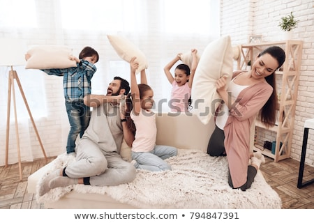 happy family having pillow fight at home Stock photo © dolgachov