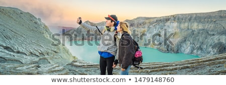 BANNER, LONG FORMAT Young tourist man and woman stand at the edge of the crater of the Ijen volcano  Stock photo © galitskaya
