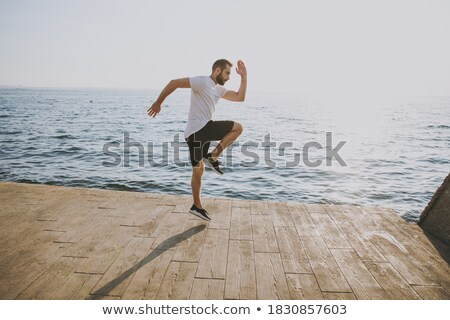 Handsome strong athletic sportsman in casual t-shirt, raise arm, tense muscle and proudly bragging g Stock photo © benzoix