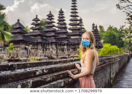 Young woman tourist in medical mask in Traditional balinese hindu Temple Taman Ayun in Mengwi. Bali, Stock photo © galitskaya