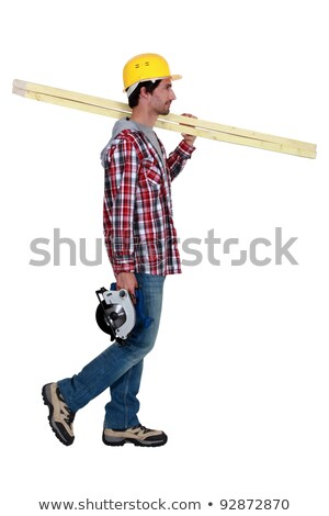 Carpenter carrying a plank of wood and a saw Stock photo © photography33