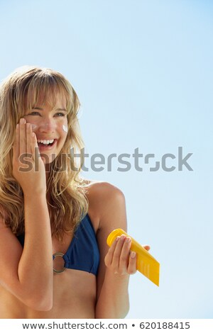 Young woman applying sunblock at the beach Stock photo © photography33