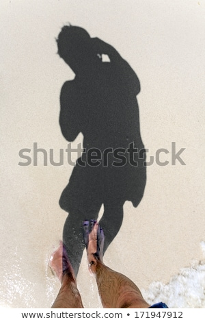 man is throwing shadow to the fine sand of the beach showing th stock photo © meinzahn