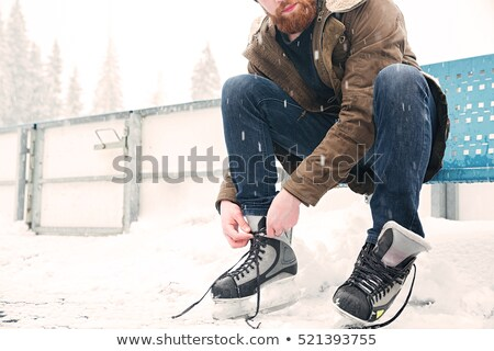 Handsome man ice skating outdoors Stock photo © deandrobot