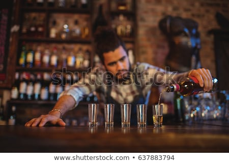 Waiter pouring cocktail drink into shot glasses at counter  Stock photo © wavebreak_media