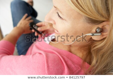 Woman sitting in chair listening to MP3 player smiling Stock photo © monkey_business