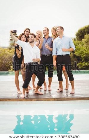 Group of friends taking selfie near poolside Stock photo © wavebreak_media