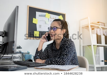 Businesswoman talking on mobile phone while working on laptop Stock photo © wavebreak_media