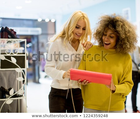 Two young multiethnic women buying purse in the store Stock photo © boggy