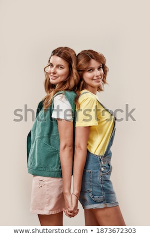 emotional young women friends posing isolated over pink background listening music with headphones stock photo © deandrobot