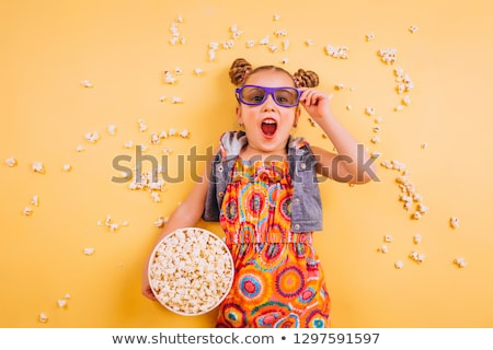 little girl with popcorn in from of tv Stock photo © Lopolo