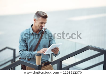 businessman with tablet pc and coffee on stairs Stock photo © dolgachov