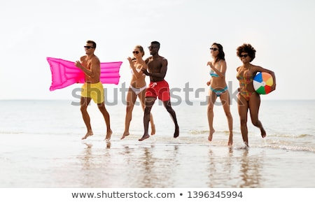 Amis courir ballon de plage natation matelas amitié Photo stock © dolgachov