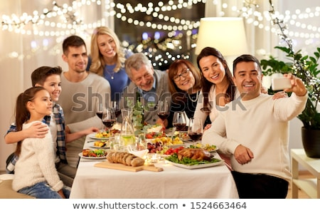 boy with smartphone at family dinner party Stock photo © dolgachov
