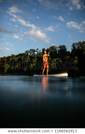 handsome young man on a paddle board getting a great exercise o stock photo © lightpoet