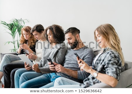 Five casual intercultural friendly millennials scrolling in their mobile gadgets Stock photo © pressmaster