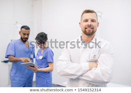 Stock photo: Young successful bearded clinician in whitecoat standing in front of camera