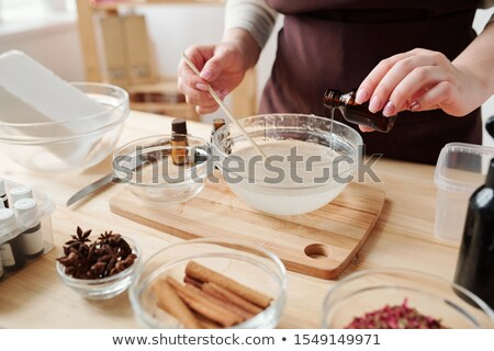 Young female pouring one of essential oils into liquid soap mass in glassware Stock photo © pressmaster