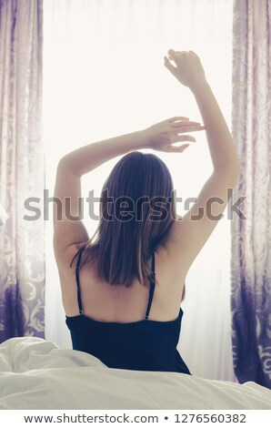 A woman with long hair and a black nightgown by the window in the house room Stock photo © ElenaBatkova