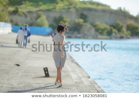 A woman walks along a concrete embankment along the sea Stock photo © ElenaBatkova
