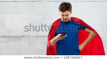 man in red superhero cape using smartphone Stock photo © dolgachov