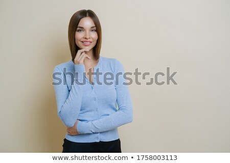 Half length shot of pretty slim woman dressed in casual blue jumper, keeps hand under chin, enjoys s Stock photo © vkstudio