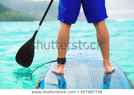 Paddle board man doing stand-up paddleboard on ocean. Athlete paddleboarding on SUP surf board on Ha Stock photo © Maridav