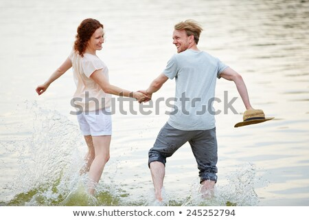 Couple running through water hand-in-hand Stock photo © photography33