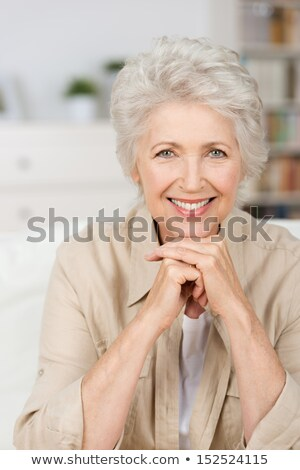 Grey-haired woman resting chin on hand Stock photo © photography33