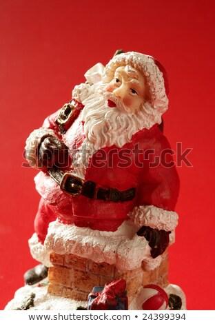 santa claus figurine over red background studio stock photo © lunamarina