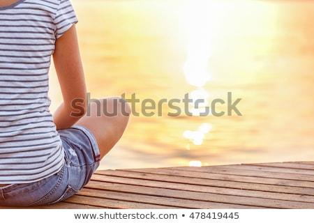 woman sitting on pier at sunrise stock photo © mike_kiev