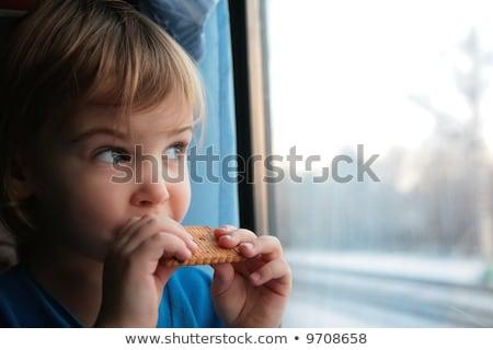 little girl eats cookies end looks in train`s window stock photo © Paha_L