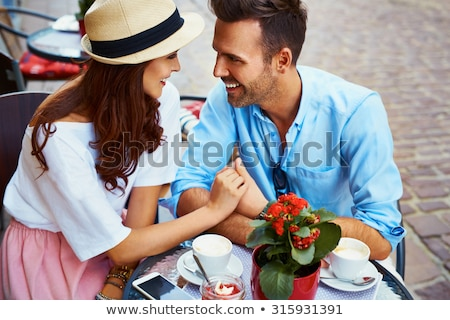 Cheerful young loving couple in cafe Stock photo © deandrobot