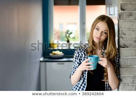 woman standing on the kitchen with warm cup of coffee stock photo © deandrobot