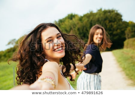 Two beautiful women walking outdoor holding hands, looking at ca Stock photo © deandrobot