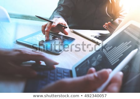finance professional working on keyboard with reports stock photo © elnur