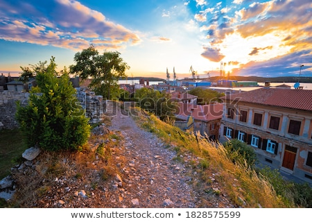 Town of Pula stone church and shipyard cranes sunset view stock photo © xbrchx