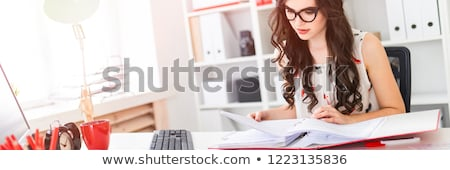 A young girl in glasses sits at a table in the office, holds a pencil in her hand and works with doc Stock photo © Traimak
