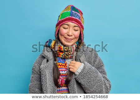 Image of two pleased girls wearing hats and scarfs smiling at ca Stock photo © deandrobot