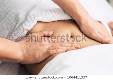 Massage therapist's massaging stomach Stok fotoğraf © Kzenon