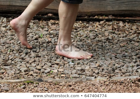 Man Walking On A Textured Cobble Pavement, Reflexology. Pebble stones on the pavement for foot refle Stock photo © galitskaya