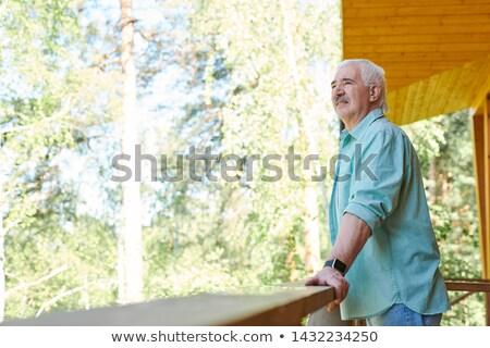 Supérieurs homme bleu shirt permanent terrasse Photo stock © pressmaster