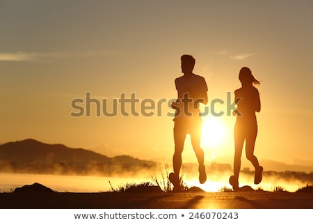 silhouette of a jogger couple in sunrise Stock photo © Lopolo