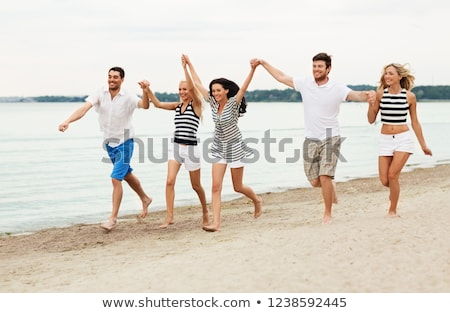 friends in striped clothes running along beach Stock photo © dolgachov
