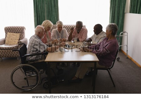 front view of group of senior people playing chess on table in living room at home stock photo © wavebreak_media