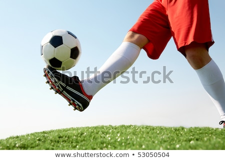 Soccer ball kick. Close up of legs and feet of football player Stock photo © matimix