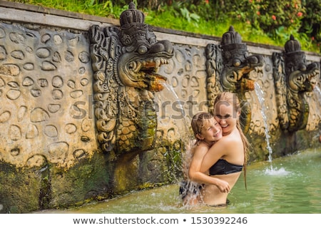 Mom and son travelers in hot springs banjar. Thermal water is released from the mouth of statues at  Stock photo © galitskaya