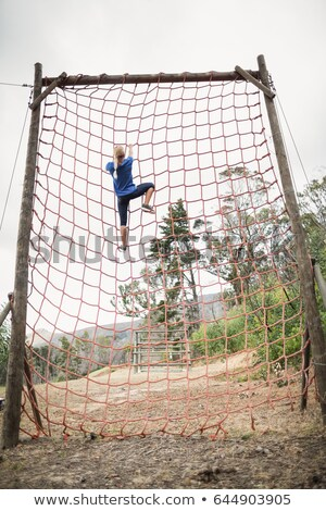 Woman climbing a net during obstacle course in boot camp Stock photo © galitskaya