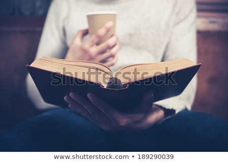 young man reading a book and drinking coffee on a couch Stock photo © photography33