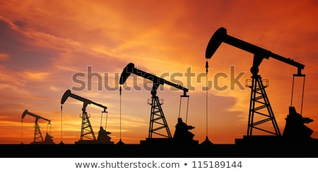 Stock photo: Oil rig silhouette, blue sky.